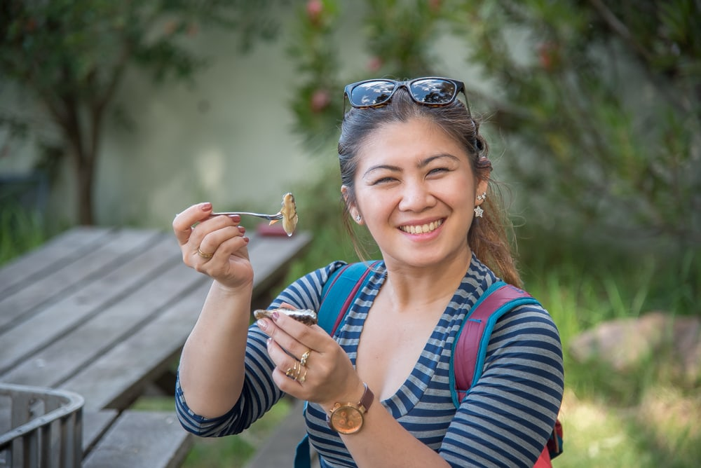 smiling woman eating a fresh oyster