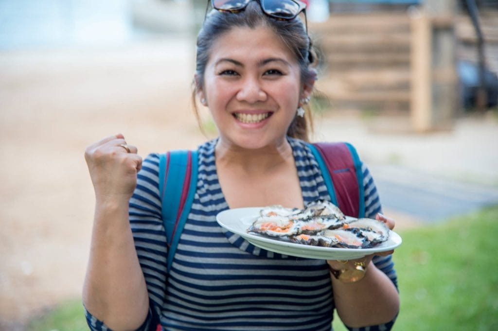 Woman holding plate of oysters pumping fist with smile on face