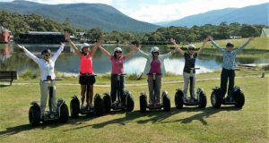 six women standing on segways with hands in the air. lake and mountains behind