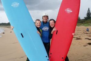 surf instructor standing between two women holding up surfboards
