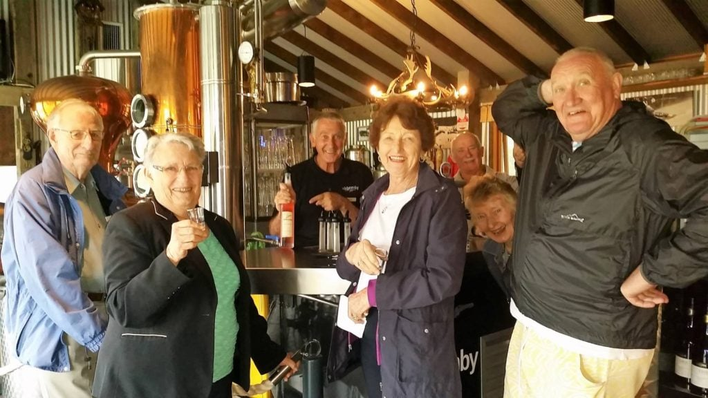 six seniors enjoying schnapps tasting at distillery