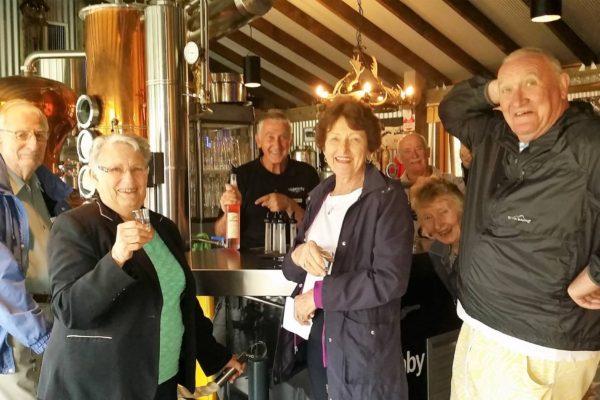 six seniors enjoying schnapps tasting at distillery