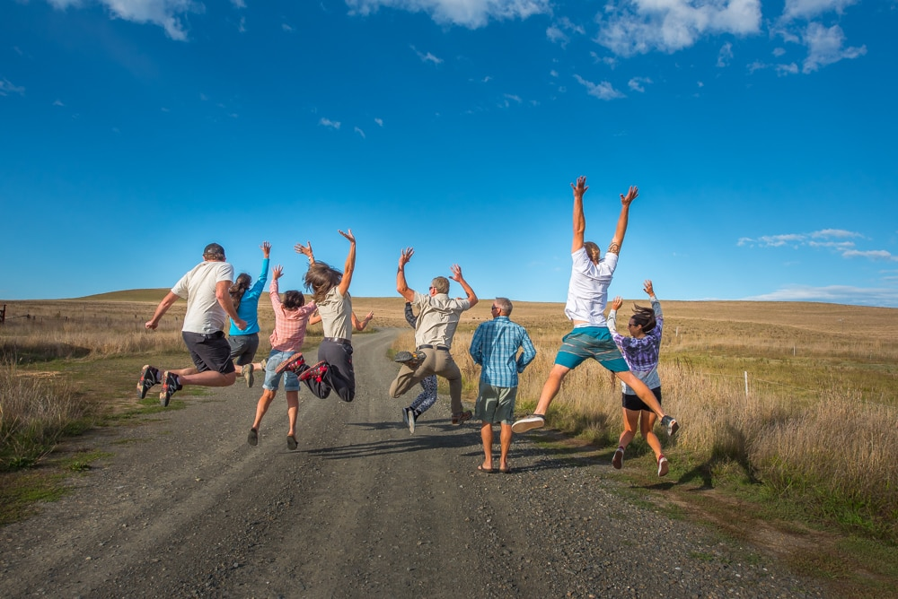 group of people from behind jumping into the air on dirt road