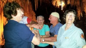 four seniors with national parks guide inside cave playing game