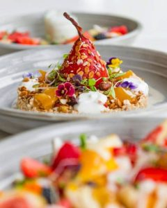 colourful poached pear dessert on plate with edible flowers