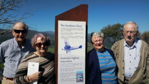 The Southern Cloud Memorial near Tumbarumba with two people standing either side and the foothills of the snowy mountains behind