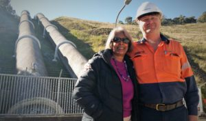 woman and snowy hydro worker standing in front of penstocks