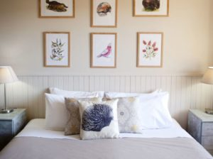 motel bed with cushions and nature prints on wall behind
