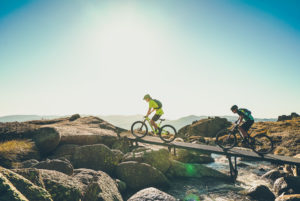 two mountain bikers crossing a bridge over a stream