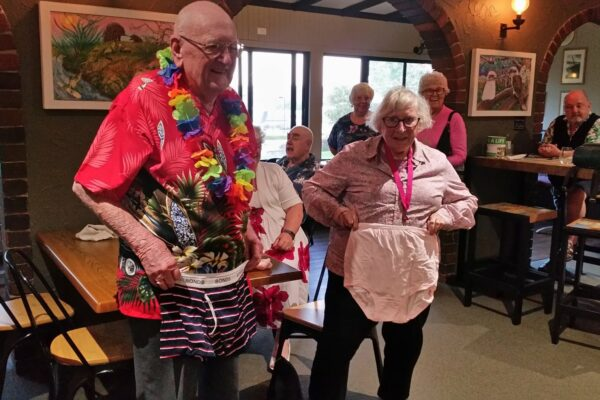 elderly man and elderly woman holding up undies in front of them