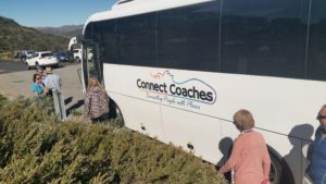 a few people in front of coach with Connect Coaches signage