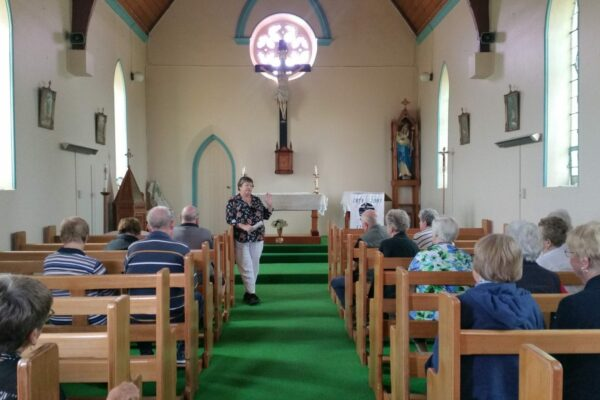 woman standing between pews in a church speaking to seated seniors