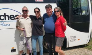 four people standing in front of a coach