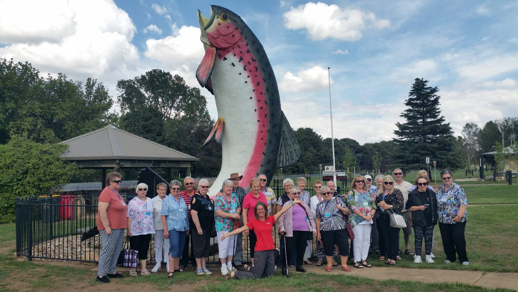 large group of seniors standing in front of a big trout