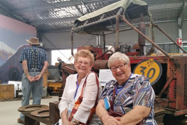 two women sitting in front of a vintage tractor