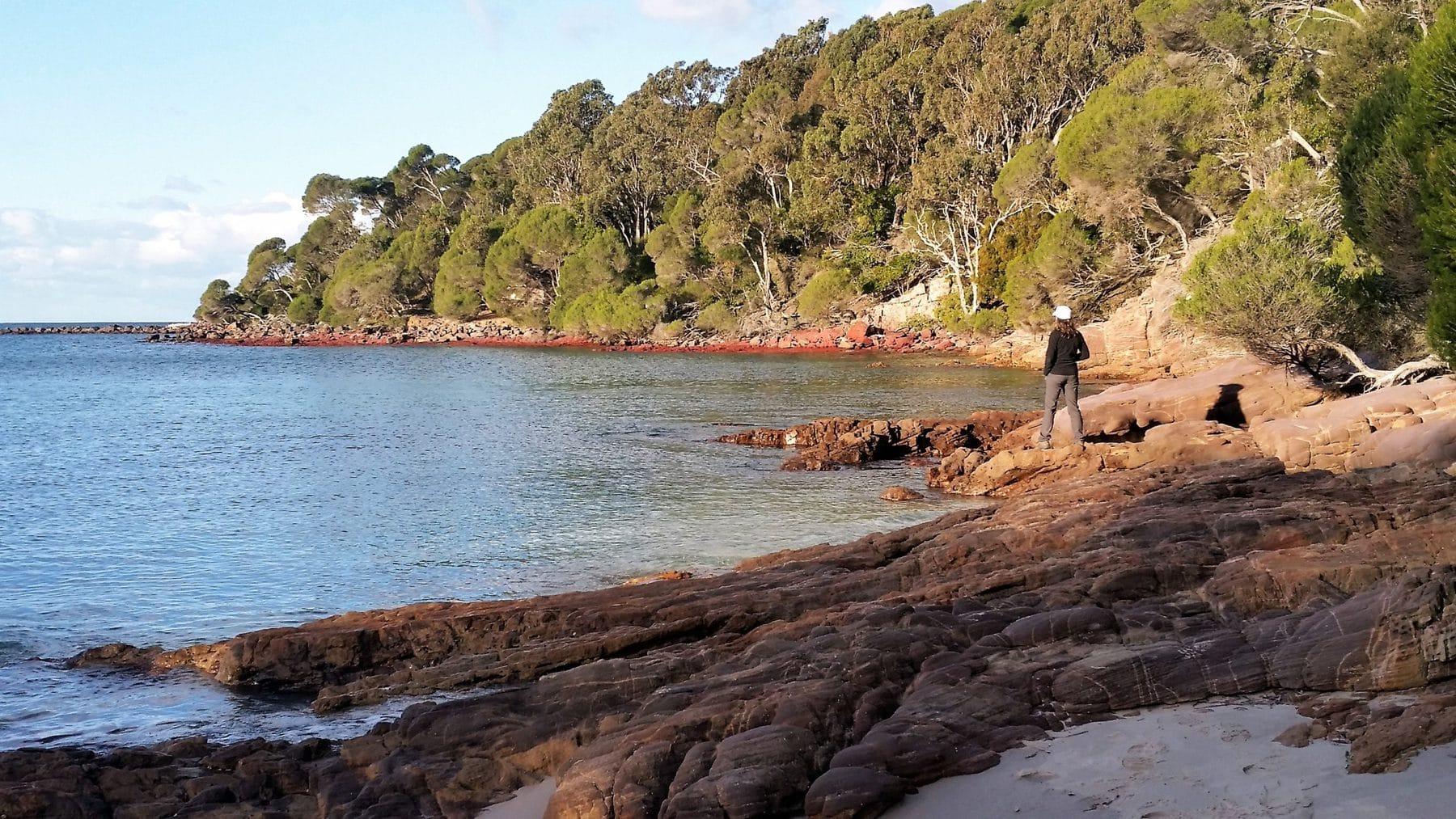 woman standing on rocks beside water in a bay