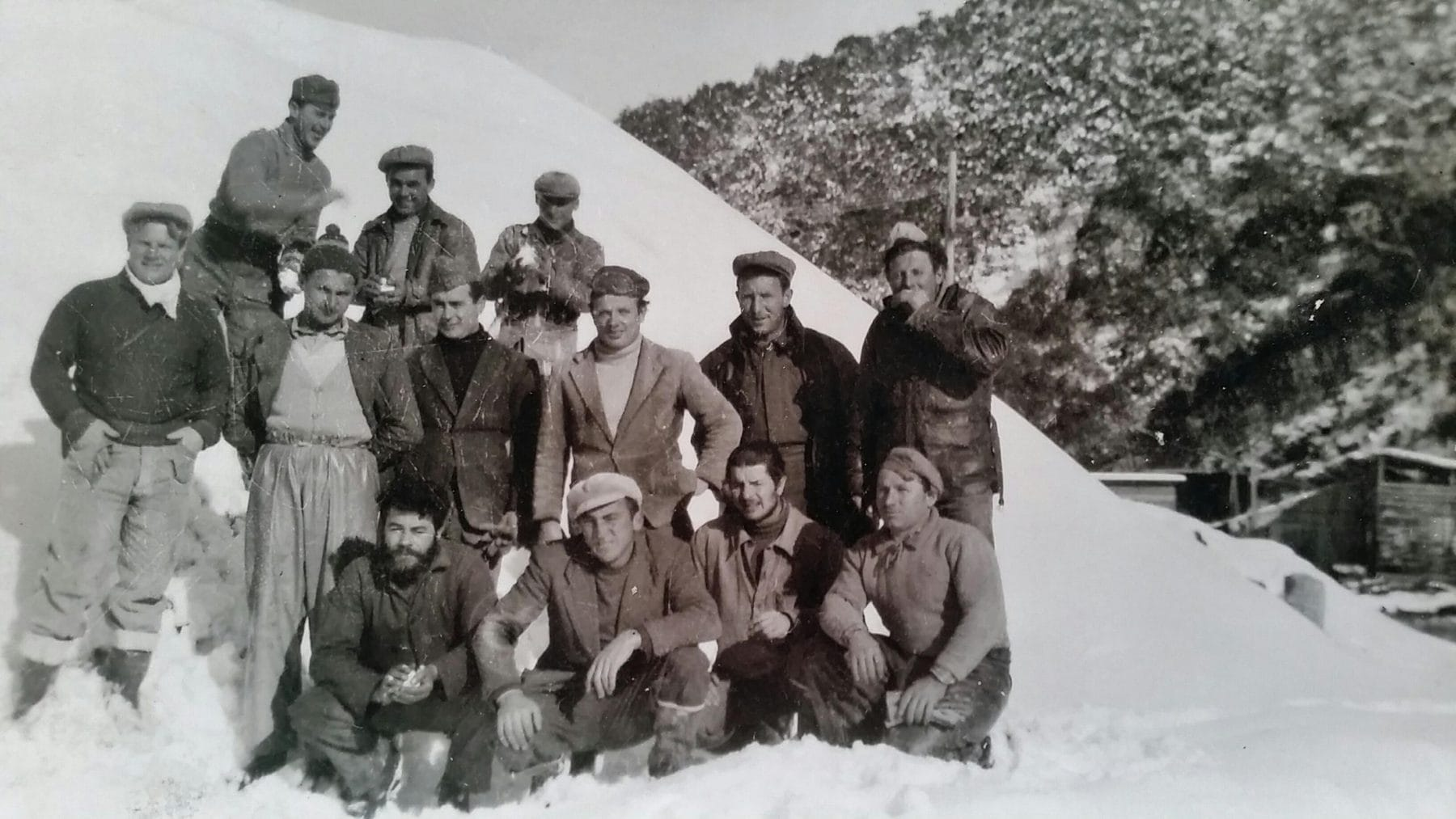 13 men in snow with mountain behind
