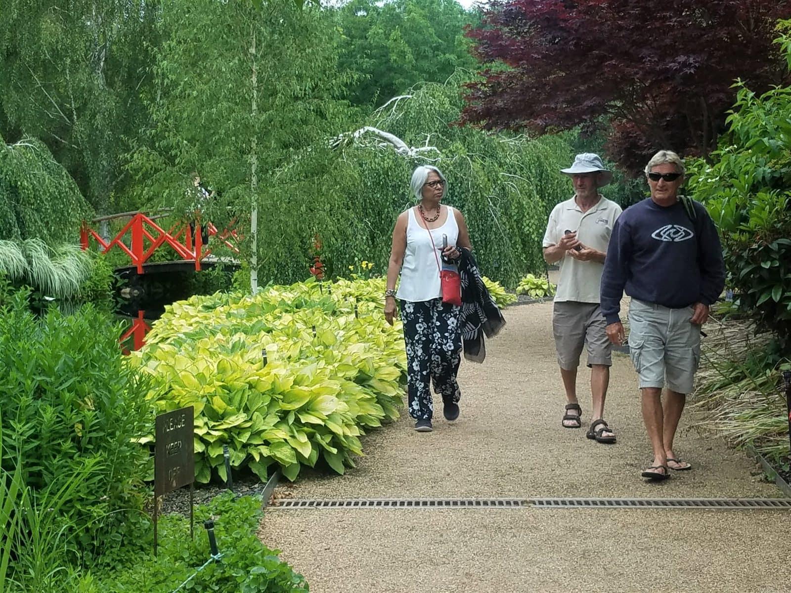 three people walking on path in lush garden with small bridge behind