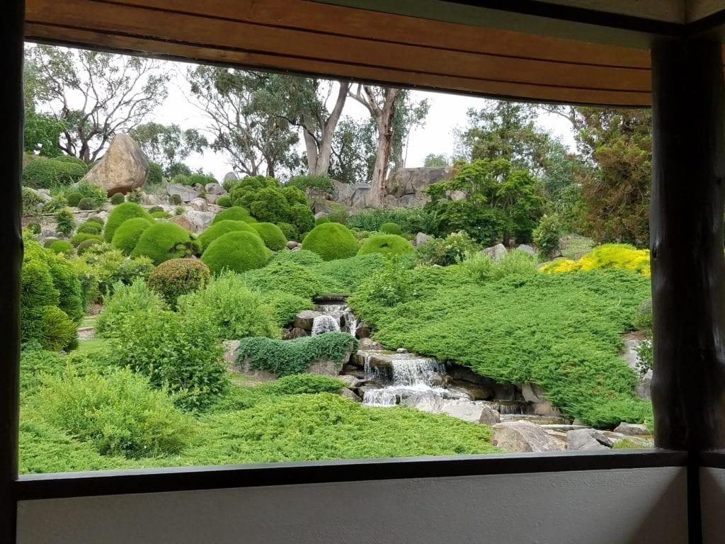 japanese garden and waterfall viewed through a window