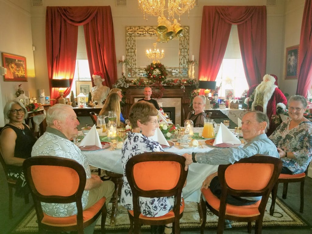 several people seated at a lavishly set dining table