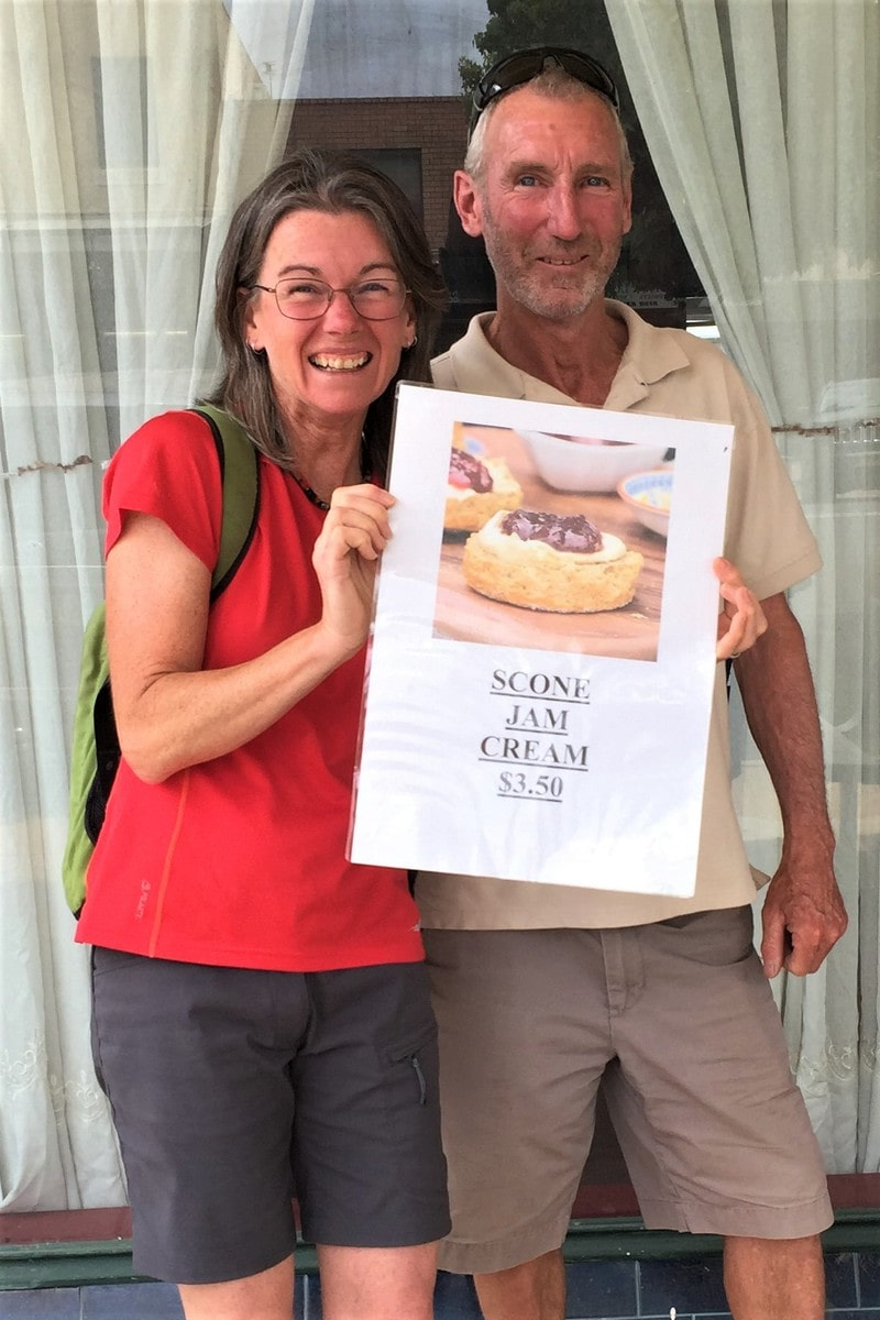Janine and Jeff holding a sign for scones jam and cream