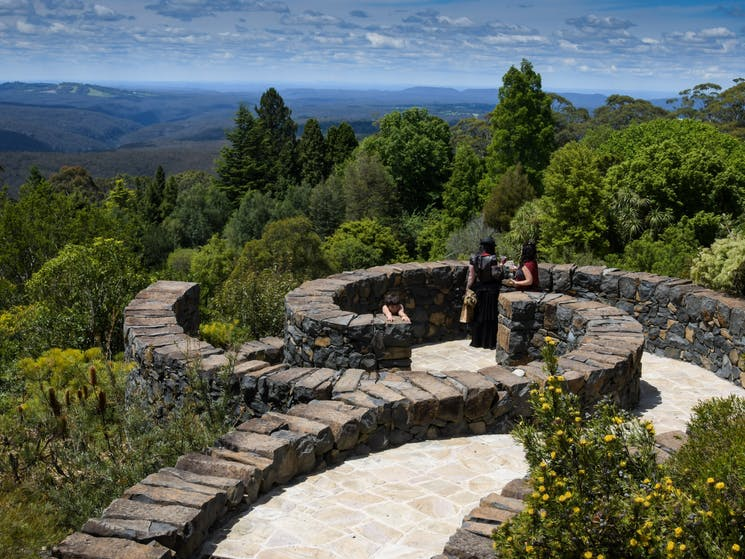 two people standing on paved stone lookout overlooking botanic garden