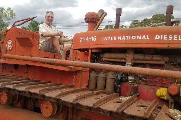 man sitting on orange diesel tractor from snowy scheme