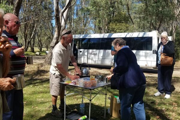 man serving morning tea to tour guests at bush campground
