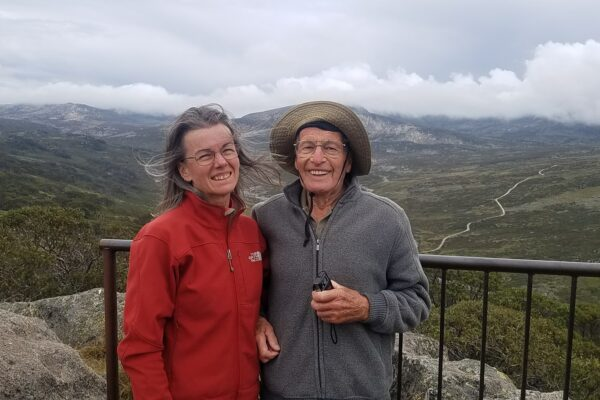 man and woman smiling at lookout with mountains behind