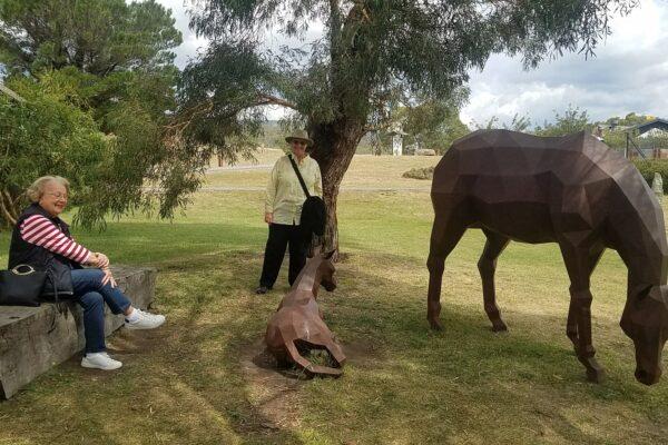 two women looking at steel horse sculptures