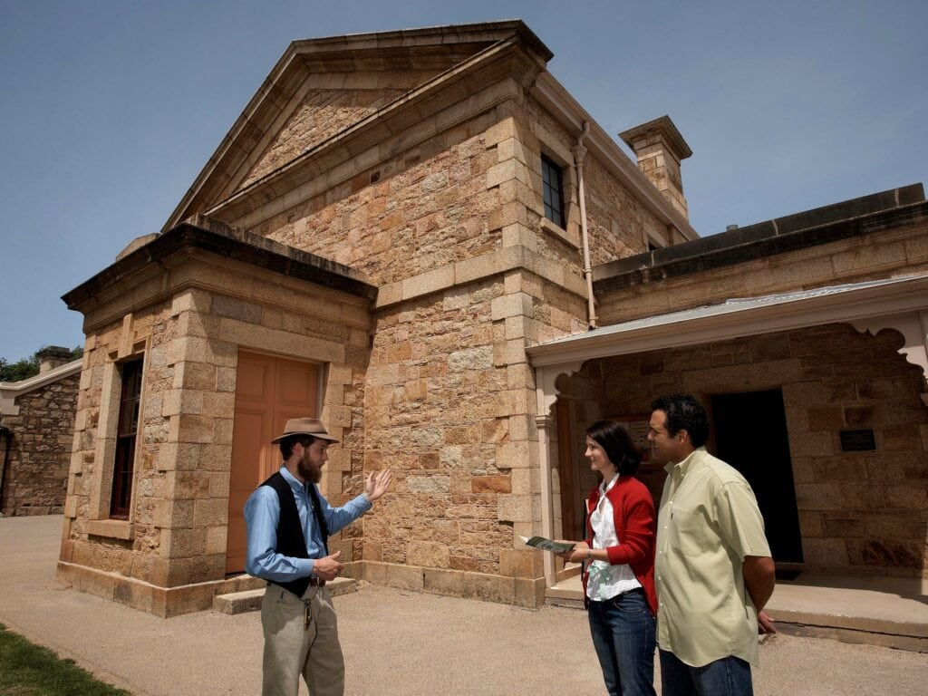 tour guide with two guests outside historic stone courthouse