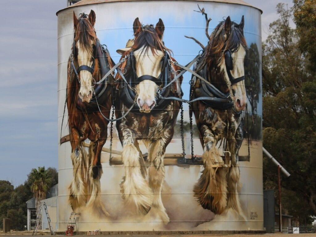 three clydesdale horses painted on a silo